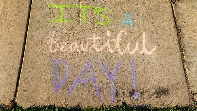 """A chalk footpath message with the words """"It's a Beautiful Day"""" written by someone performing an act of kindness while stuck at home."""