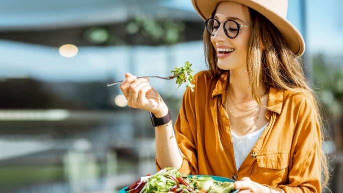 Young woman enjoying a plate of salad at an outdoor cafe