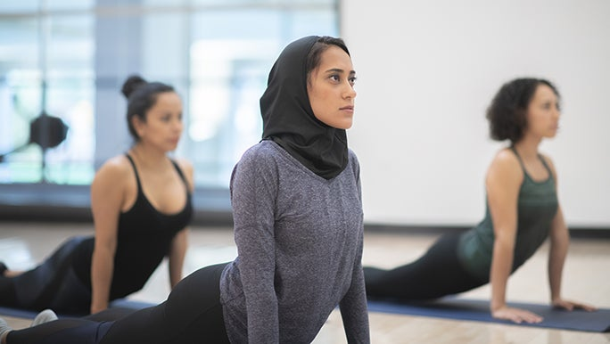 Three women do Yoga in a group lesson. Each person has chosen different types of clothing for their Yoga class.