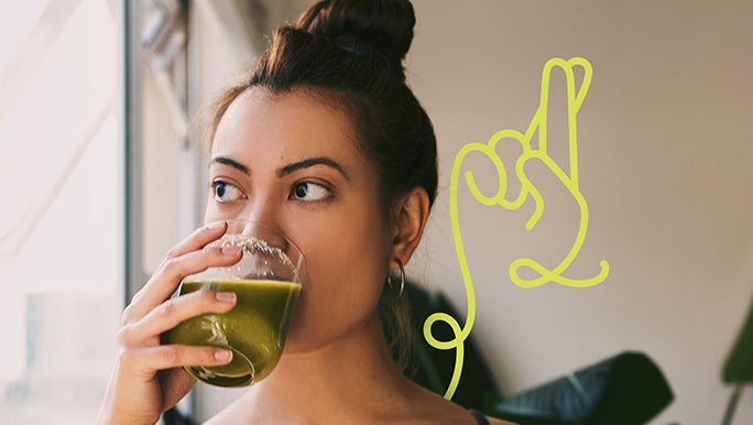 Young woman drinking a fresh green juice first thing in the morning