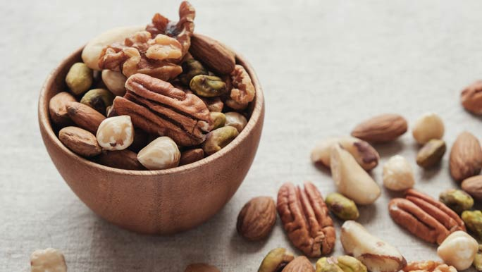 Mixed raw nuts in a small wooden bowl