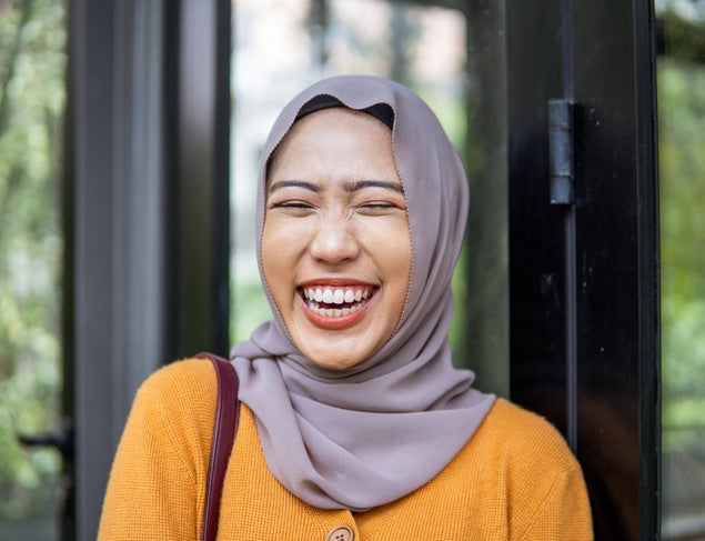 Happy young woman in a hijab and yellow cardigan laughing