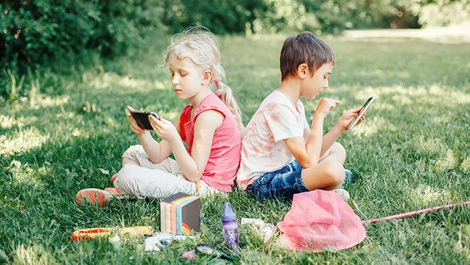 Two kids sit outside on the grass with their butterfly catching nets around them but they are both playing on their phones while you wonder how much screen time should kids have.