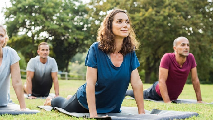Woman and men in the park doing yoga, the are forming healthy habits.