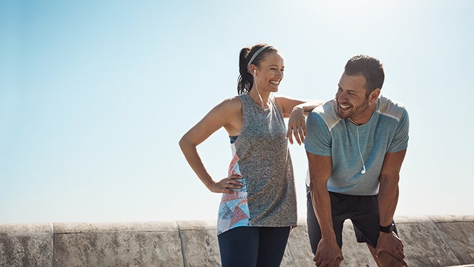 Two people in exercise clothes smiling after they have finished their workout which may have effects on the immune system.
