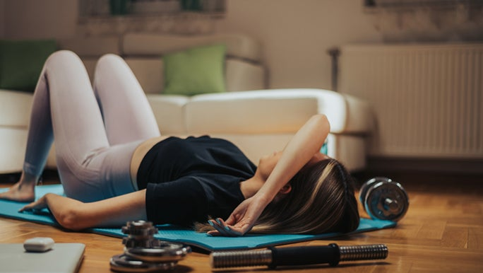A lady lays on the floor, her muscles hurt after exercise.