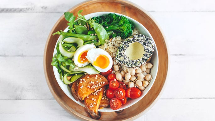 Salad bowl with fresh greens, roasted sweet potato, chickpeas, tomatoes and avocado