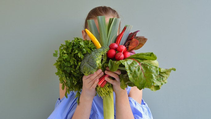 Girl holding a bunch of colourful vegetables in front of her face