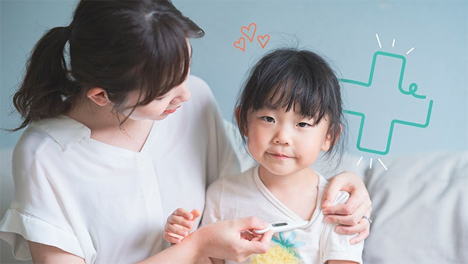 A young mother is checking her daughter's temperature with an underarm thermometer