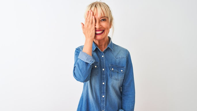 Middle age woman wearing casual denim shirt standing covering one eye with hand, confident smile on face and surprise emotion