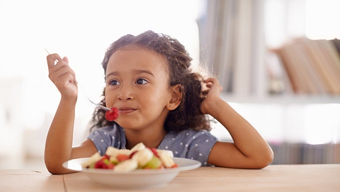 A kid eats a bowl of fruit salad for breakfast, she looks happy.