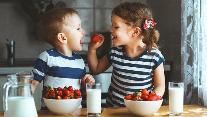 Two toddlers a boy and a girl in blue and white stripe tops eating strawberries in the kitchen