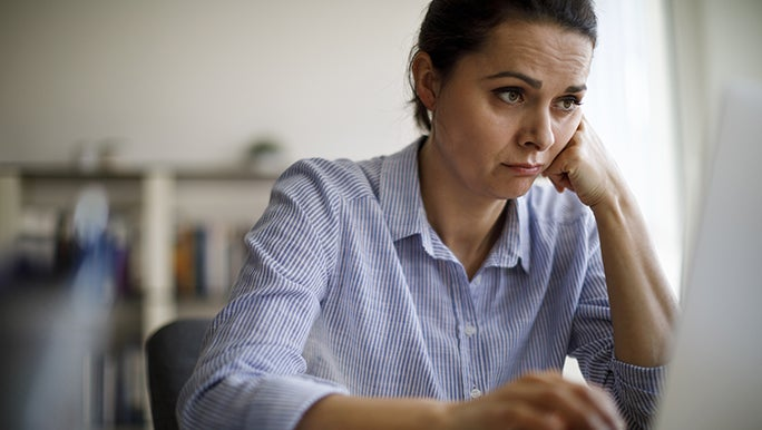 A woman leans her cheek on her closed fist, she looks to be experiencing brain fog while staring at a laptop screen.