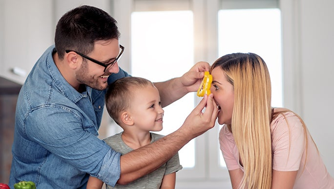 A child is watching his father hold a vegetable piece up to his mother's eye as she plays along with the game as a way of making vegetables fun.