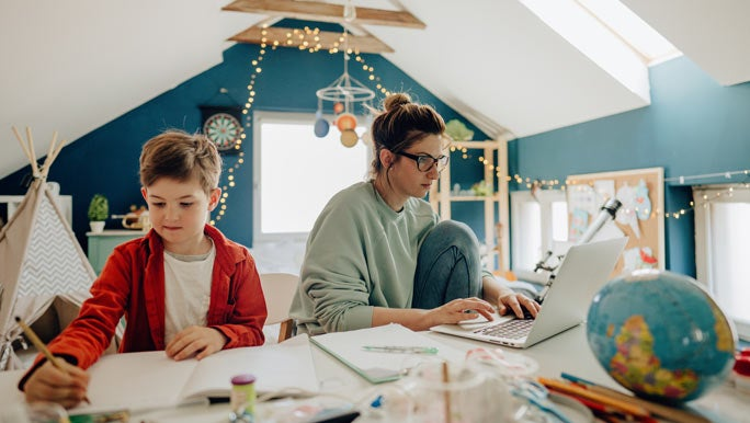 Mum working from home on a laptop next to her son doing his schoolwork