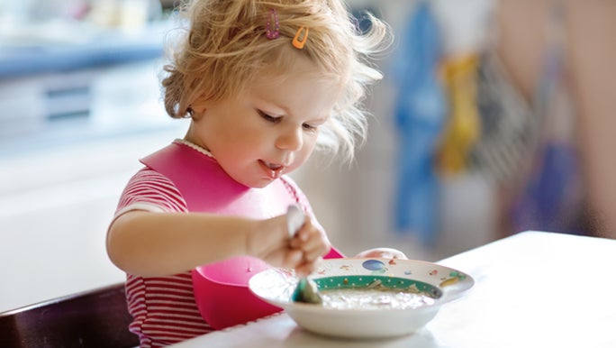 A toddler eats a bowl of oats at a kitchen bench. She has a pink rubber bib on.