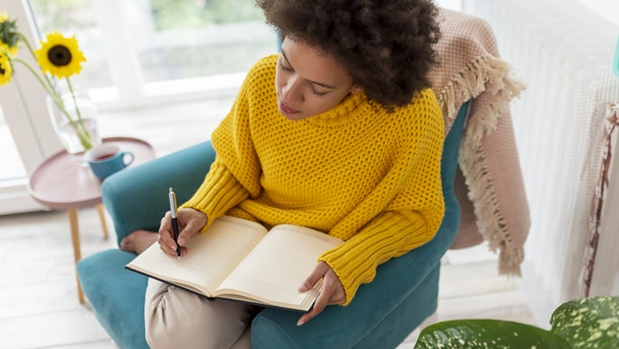 A lady in a bright yellow jumper is sitting on a blue armchair and updating her daily planner.