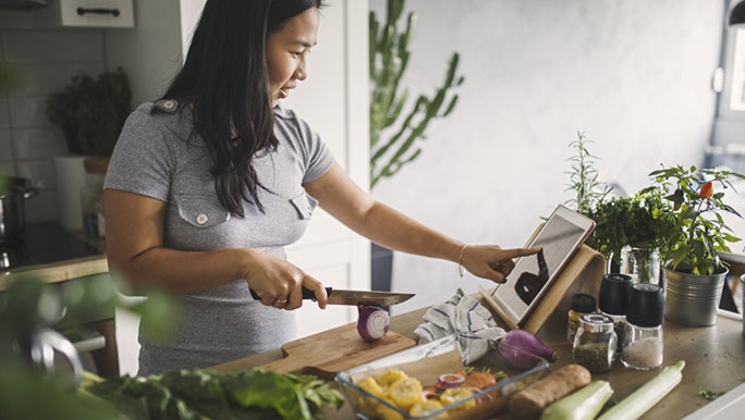 A woman stands in a kitchen preparing a healthy meal from a recipe. Perhaps she is using nutrition as a motivation to lose weight.