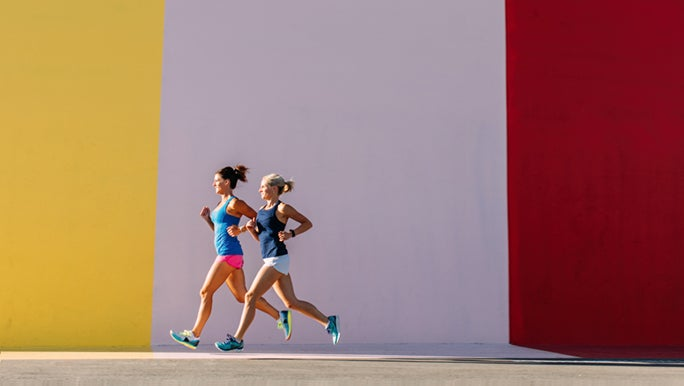Two women run in front of a colourful wall.