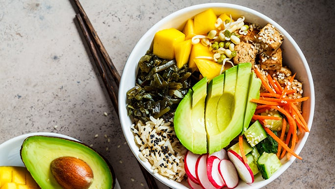 From above, a plant based or vegan bowl of rice and vegetables is on a table next to some chopsticks.