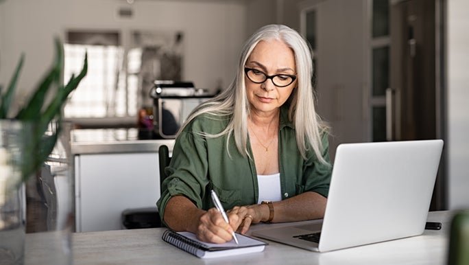 A woman with long grey hair is sitting at a desk in front of a laptop. She is writing in her daily planner/diary.