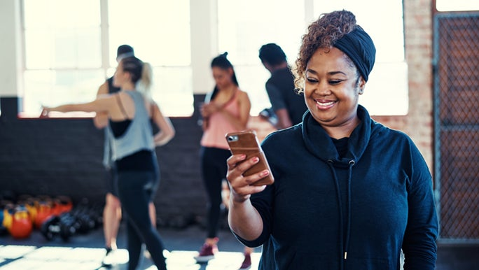 A woman is smiling whilst she looks down at her phone, she just finished her workout and is excited to know this is good for her well-being.