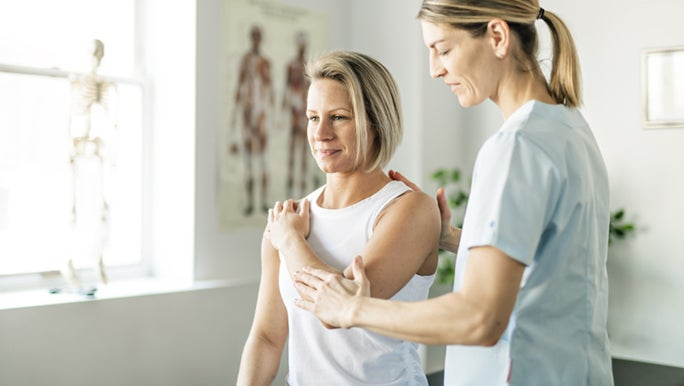 A woman is stretching her shoulder with the help of a physiotherapist. They may be discussing why stretching is important.