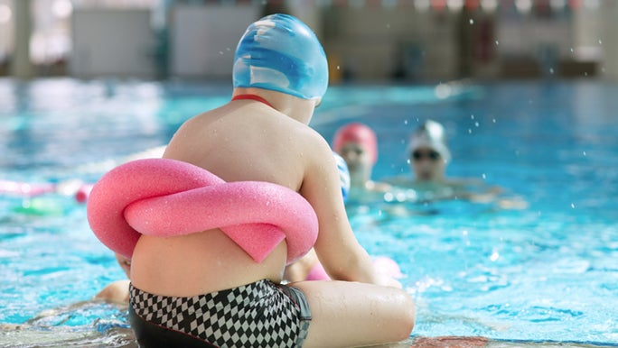 Child sits at the pool's edge, he has a pink pool noodle tied around his middle. Swimming is such a fun exercise for kids.