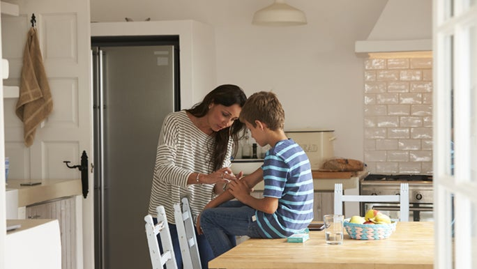 A mother is putting a bandaid on her son's arm. She got it from her home first aid kit.