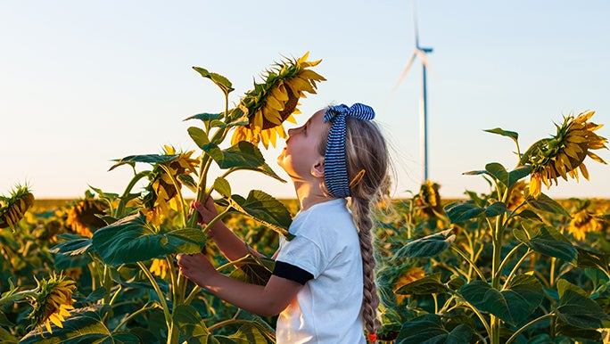 A girl is smelling a sunflower in a large field of sunflowers looking very happy which may be a benefit of nature play for children.