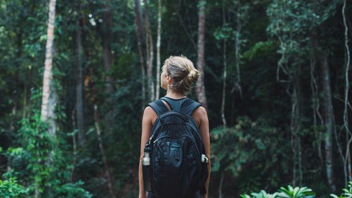 Woman walking in the bush stopping to take her surroundings