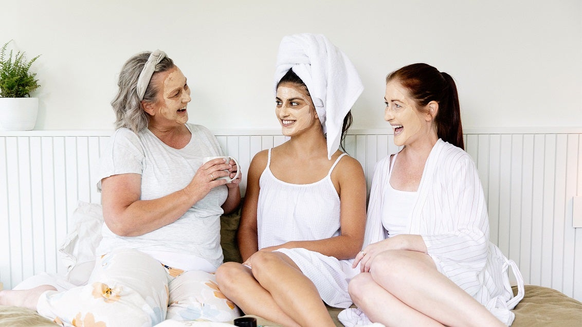 Three happy female friends doing facials at home with The Herb Farm skincare products