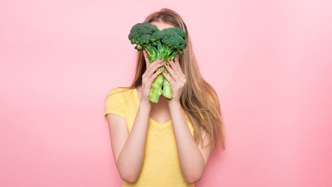 Young woman in a yellow t-shirt holding a bunch of broccoli in front of her face