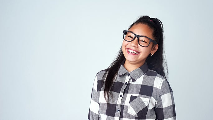 A tween with thick black glasses smiles directly into the camera.