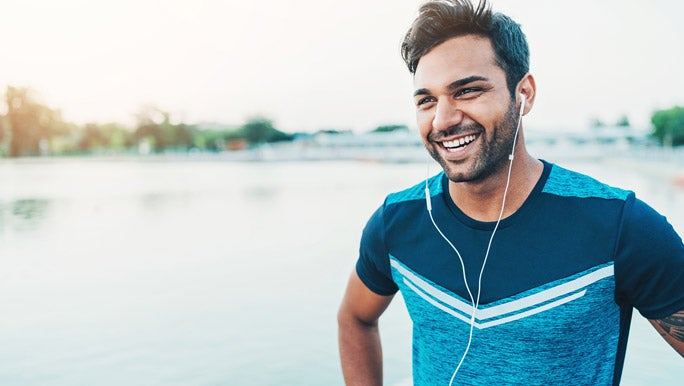 Smiling young man listening to music enjoying outdoor exercise
