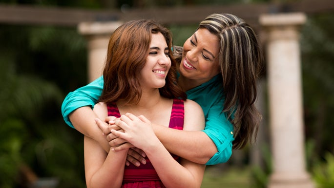Mother and daughter are standing outside, her mother hugging her from behind as they smile. Her mother reminded her how difficult pimples can be as a teenager.