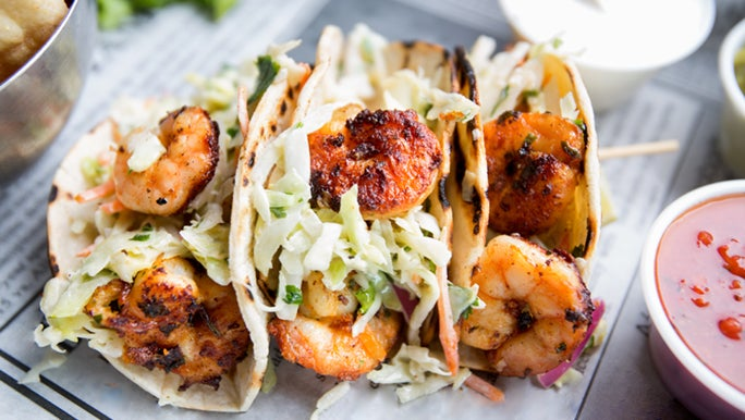 Three prawn and slaw tacos on a plate. This is a better food choice than regular tacos.