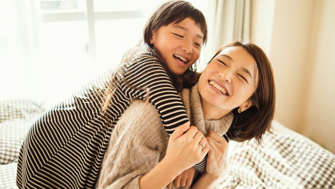 Young mum playing and enjoying time with her daughter at home