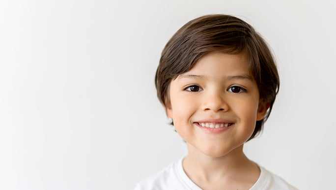 A young boy in a white shirt smiles directly into the camera. He is in front of a white wall. He looks grateful.