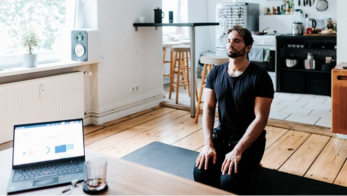 A man is on his knees in a living room on a black yoga mat, he is meditating for energy.