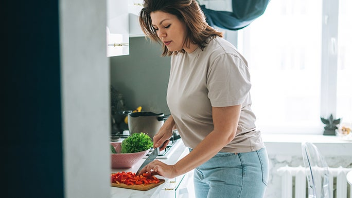 A woman cuts vegetables in her kitchen, she is exploring the benefits of fermented foods.