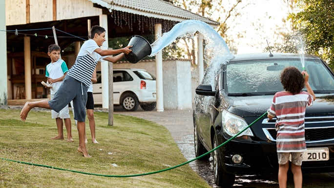 A family is getting some incidental exercise by washing the car. A teenager is throwing a bucket of water in the air, and a child is spraying the car with a hose.