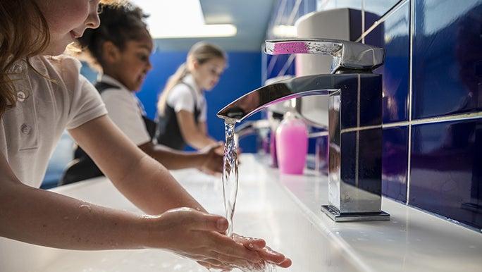 Three children wash their hands in a school bathroom.