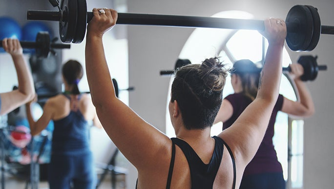 A woman in a gym class is lifting a weighted bar above her head and enjoying the benefits of lifting weights.