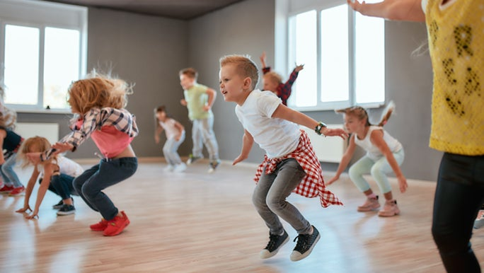 An action shot of children jumping in the air in an exercise class for kids.