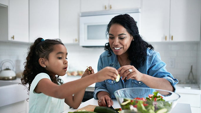 A mother prepares a salad with her daughter. The benchtop is full of seasonal fruit and vegetables.