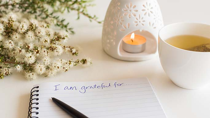 An open gratitude journal lays on a table next to an oil burner and a cup of herbal tea. The words, I am grateful for, are written in blue pen on the page.