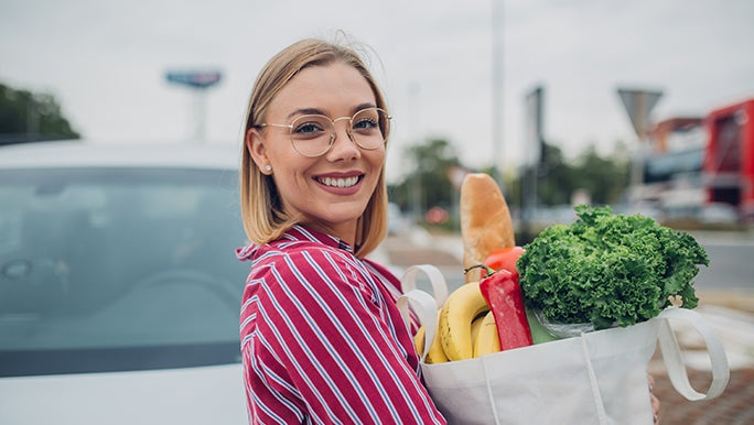 Holding her shopping in a reusable bag, a woman looks happy because she bought vegetables in season in Australia.