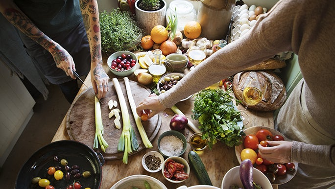 A wooden table is covered with plant based and vegan ingredients. There is someone cooking.