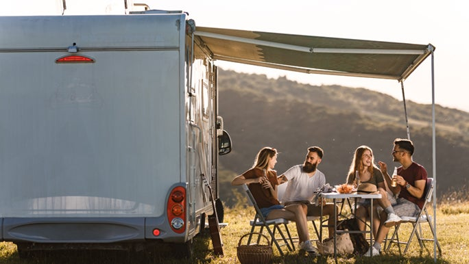 Two couples enjoy a sunset picnic next to a caravan, perhaps they know that social relationships benefit their health.